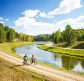 Junge Fahrräder des glücklichen Paars Reitdurch den Fluss Stockbilder