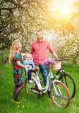 Junge Familie auf einem Garten der Fahrräder im Frühjahr Lizenzfreies Stockfoto