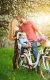 Junge Familie auf einem Garten der Fahrräder im Frühjahr Lizenzfreie Stockbilder