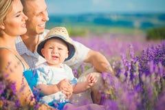 Junge Familie auf einem Lavendelgebiet Stockfoto