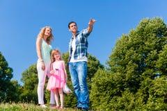 Junge Familie auf Feld, Vati, der auf etwas zeigt Stockfoto