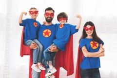 Junge Familie in den roten und blauen Klagen von Superhelden Ihre Gesichter in den Masken und in ihnen sind in den Regenmänteln Stockbild