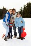 Junge Familie in der alpinen Schnee-Szene mit Schlitten Stockfotografie