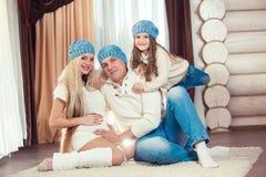 Junge Familie, die auf Boden sitzt in einer Winterstrickjacke und -hut das Konzept von Weihnachten Schwangerschaft in einem Holzh Stockfotos