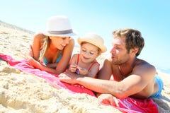 Junge Familie, die auf dem Strand liegt und spielt Lizenzfreie Stockfotografie