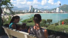 Junge Familie, die auf der Bank auf dem Hügel übersieht das Meer stillsteht stock video