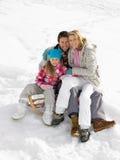 Junge Familie, die auf einem Schlitten im Schnee sitzt Lizenzfreies Stockbild