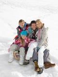 Junge Familie, die auf einem Schlitten im Schnee sitzt Lizenzfreie Stockfotos