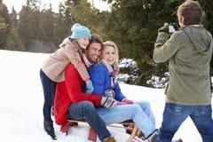 Junge Familie, die auf einem Schlitten im Schnee sitzt Stockfoto