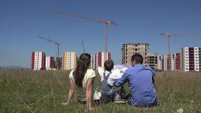 Junge Familie, die auf grünem Gras sitzt und Bauvorhaben betrachtet und, errichtendes neues Leben neues Wohnblock stock video footage