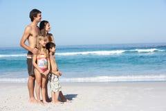 Junge Familie, die auf Sandy-Strand am Feiertag steht Lizenzfreie Stockfotos