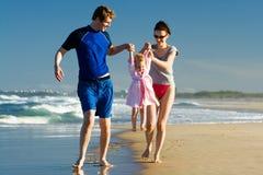 Junge Familie, die das Kind carying ist Lizenzfreie Stockfotos