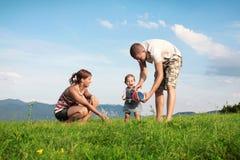 Junge Familie, die in der Natur spielt Lizenzfreie Stockbilder