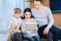 Junge Familie, die durch das Video überrascht ist stockfotografie