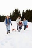 Junge Familie, die durch Schnee mit Schlitten läuft Stockbilder