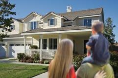 Junge Familie, die ein neues Haus betrachtet Lizenzfreie Stockbilder