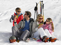 Junge Familie, die ein Picknick auf Ski-Ferien teilt Lizenzfreie Stockfotos