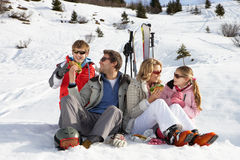 Junge Familie, die ein Picknick auf Ski-Ferien teilt Stockbilder
