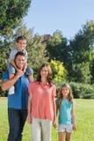 Junge Familie, die in einem Park aufwirft Stockfotos