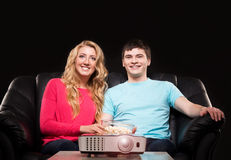 Junge Familie, die einen Film oder eine Sportsendung auf einem Laser-Projektor aufpasst lizenzfreie stockfotografie