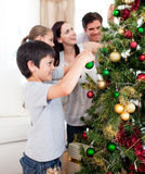 Junge Familie, die einen Weihnachtsbaum verziert Lizenzfreies Stockbild