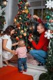 Junge Familie, die einen Weihnachtsbaum verziert Lizenzfreie Stockbilder