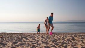 Junge Familie, die Fußball auf dem Strand spielt