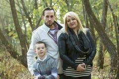 Junge Familie, die im Fallwald stillsteht Stockbild