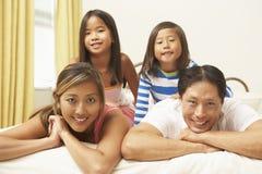 Junge Familie, die im Schlafzimmer sich entspannt Stockbild