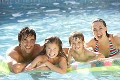 Junge Familie, die im Swimmingpool sich entspannt Stockfoto