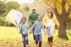 Junge Familie, die mit einem Drachen spielt Lizenzfreie Stockfotos