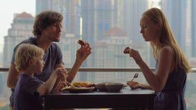 Junge Familie, die, Mittagessen auf ihrem Balkon in einem Wolkenkratzer mit einer Ansicht über ein Ganzstadtzentrum der Stadt frü stock footage