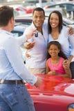 Junge Familie, die neues Auto aufhebt Stockfotografie