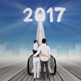 Junge Familie, die Nr. 2017 und Rolltreppe betrachtet Stockbild