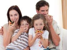 Junge Familie, die Pizza isst Stockfotografie