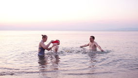 Junge Familie, die rotes Spielzeugboot bei Sonnenuntergang spielt stock footage