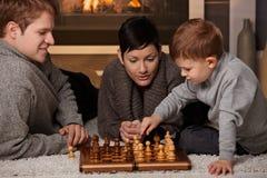 Junge Familie, die Schach spielt Lizenzfreie Stockfotos