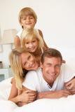 Junge Familie, die sich zusammen im Bett entspannt Stockbild