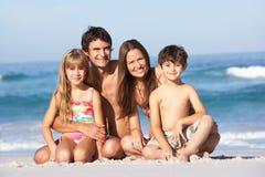 Junge Familie, die am Strand-Feiertag sich entspannt Stockfotografie