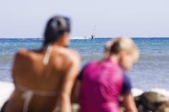 Junge Familie, die am Strand sitzt und ihren Feiertag genießt Stockfotografie