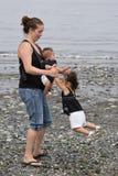 Junge Familie, die am Strand spielt Lizenzfreie Stockfotografie