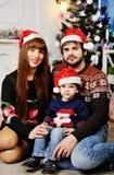 Junge Familie, die unter dem Weihnachtsbaum sitzt lizenzfreie stockbilder