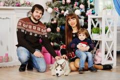 Junge Familie, die unter dem Weihnachtsbaum sitzt lizenzfreie stockfotografie