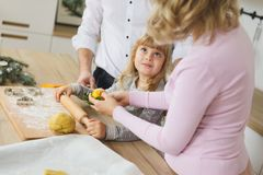 Junge Familie, die zu Hause Plätzchen macht Herstellung eines Lebkuchenplätzchens mit den Kindern zur Weihnachtszeit Lizenzfreies Stockbild