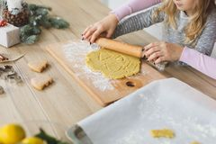 Junge Familie, die zu Hause Plätzchen macht Herstellung eines Lebkuchenplätzchens mit den Kindern zur Weihnachtszeit Stockfotografie