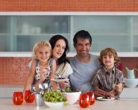 Junge Familie, die zuhause an der Kamera lächelt Stockfoto