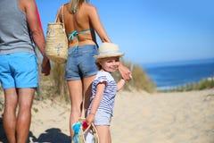 Junge Familie, die zum Strand an einem heißen Sommertag geht Lizenzfreie Stockfotografie