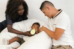 Junge Familie Eltern, die ein Säuglingskind mit Milch einziehen Frauklo lizenzfreie stockfotografie