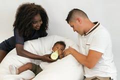 Junge Familie Eltern, die ein Säuglingskind mit Milch einziehen Frauklo stockfotografie