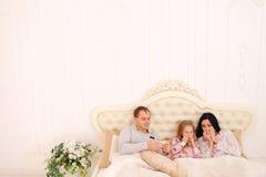 Junge Familie erhielt krankes oder krankes im Bett zu Hause niesen Stockfotografie